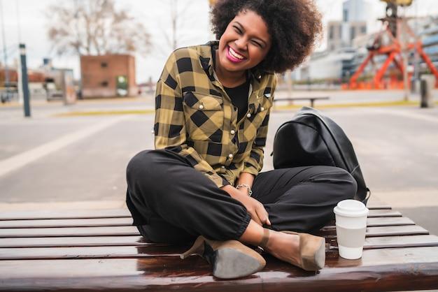 Portret van mooie afro amerikaanse latijns-vrouw zitten met een kopje koffie buiten in de straat. stedelijk concept. Gratis Foto