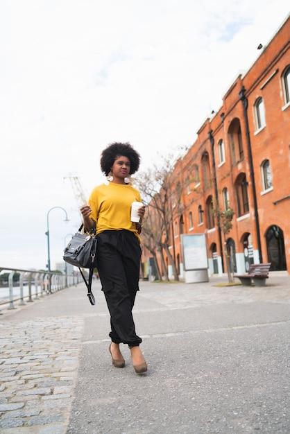 Portret van mooie afro amerikaanse vrouw lopen en houden een kopje koffie buiten in de straat. stedelijk concept. Gratis Foto