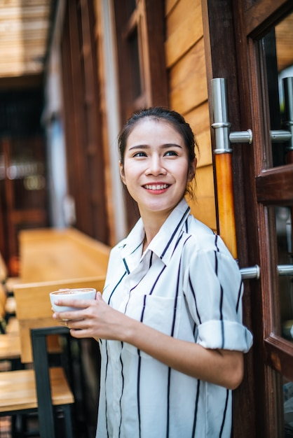 Portret van mooie aziatische vrouw ontspannen in café Gratis Foto