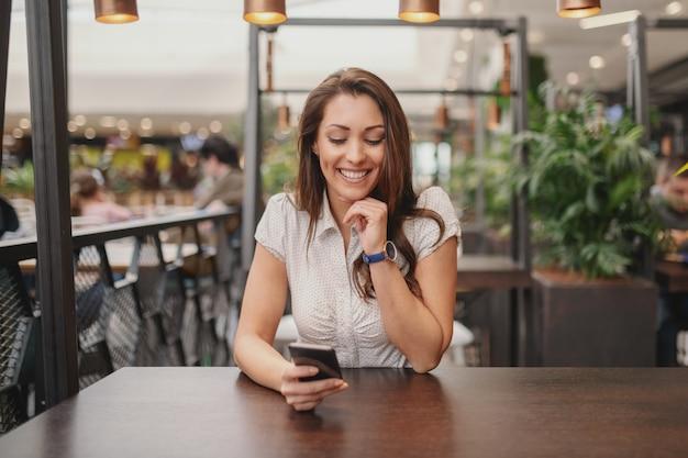 Portret van mooie blanke brunette zitten in cafe en bericht lezen op slimme telefoon. Premium Foto