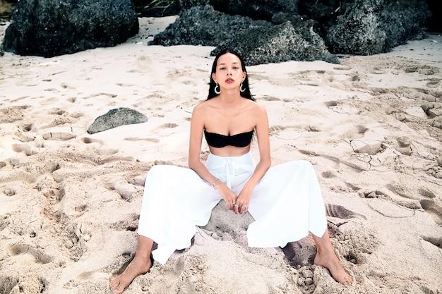 Portret van mooie blanke vrouw model met donker lang haar in wijde pijpen klassieke broek zittend op zomer strand met wit zand in de buurt van rotsen Gratis Foto