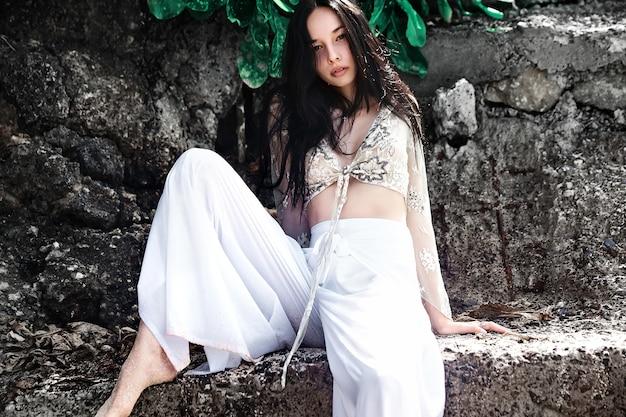 Portret van mooie blanke vrouw model met lang donker haar in wijde pijpen klassieke broek poseren in de buurt van rotsen en groene tropische exotische bladeren achtergrond Gratis Foto