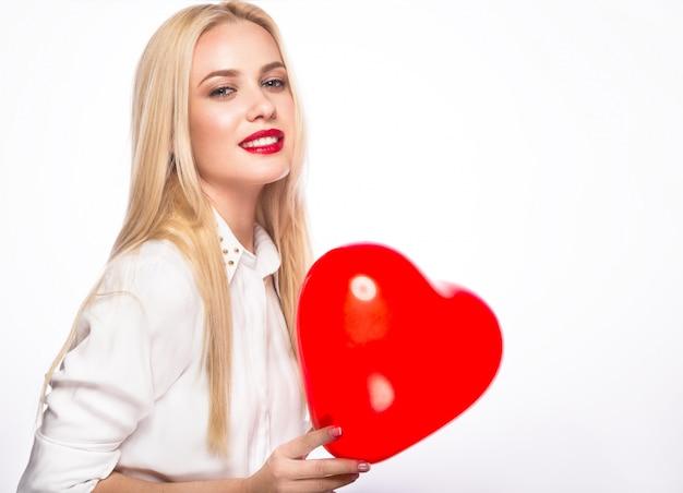 Portret van mooie blonde vrouw met heldere make-up en rood in hand hart Premium Foto