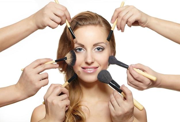 Portret van mooie blonde vrouw met lang haar en make-upborstels dichtbij aantrekkelijk gezicht Gratis Foto