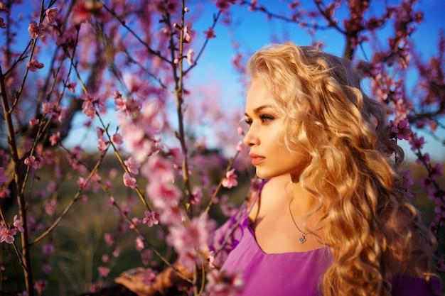 Portret van mooie blondevrouw in bloeiende roze tuin Premium Foto