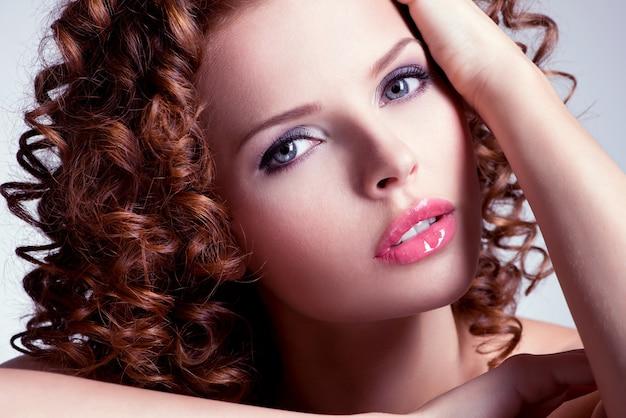 Portret van mooie brunette jonge vrouw met lichte make-up. close-upgezicht met krullend kapsel. Gratis Foto