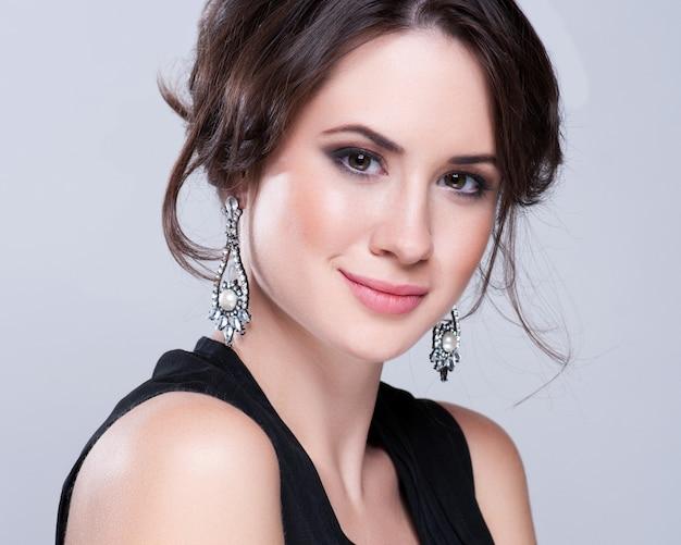 Portret van mooie brunette vrouw in zwarte jurk. cosmetische oogschaduw. Premium Foto