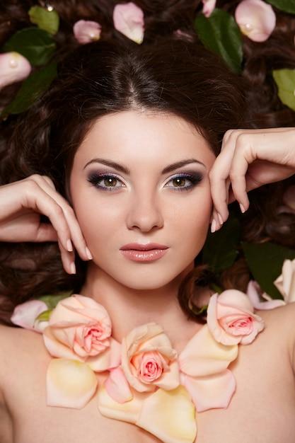 Portret van mooie donkerbruine vrouw met lang krullend haar en heldere make-up witjh bloemen in haar Gratis Foto