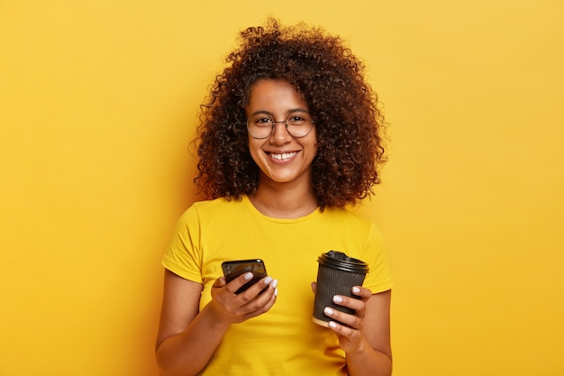Portret van mooie duizendjarige vrouw houdt smartphone en drinkt afhaalmaaltijden koffie, lacht aangenaam, draagt gele t-shirt, vraagt nummer om later te ontmoeten Gratis Foto