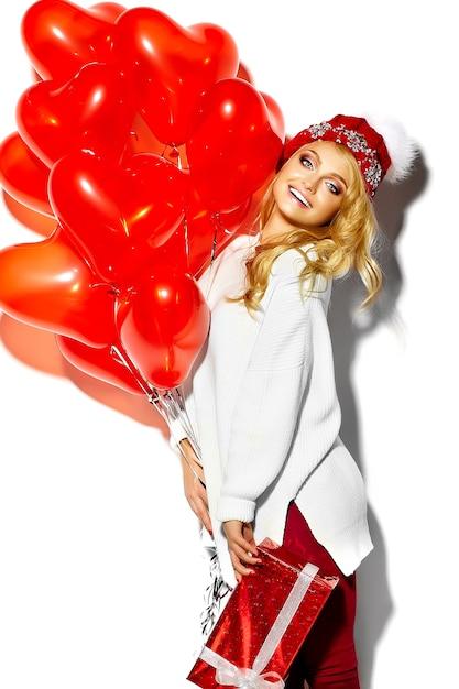 Portret van mooie gelukkig lieve lachende blonde vrouw meisje houdt in haar handen grote kerstcadeau doos en hart ballonnen in casual rode hipster winterkleren, in witte warme trui Gratis Foto
