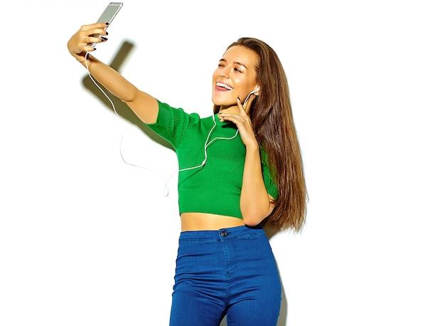 Portret van mooie gelukkig schattige brunette vrouw meisje in casual groene hipster zomer kleding zonder make-up op wit wordt geïsoleerd, neem een selfie en toont haar tong Gratis Foto