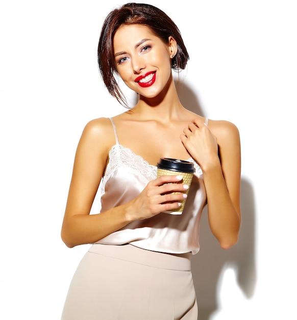 Portret van mooie gelukkig schattige sexy brunette vrouw met rode lippen in brede klassieke broek met plastic koffiekopje op witte achtergrond Gratis Foto