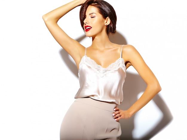 Portret van mooie gelukkig schattige sexy brunette vrouw met rode lippen in brede klassieke broek op witte achtergrond Gratis Foto