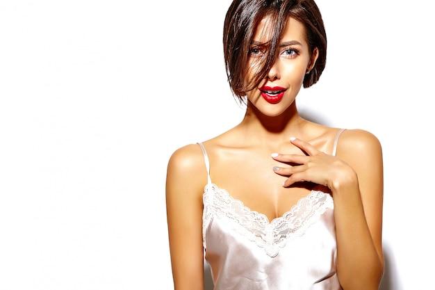Portret van mooie gelukkig schattige sexy brunette vrouw met rode lippen in pyjama's lingerie op witte achtergrond Gratis Foto