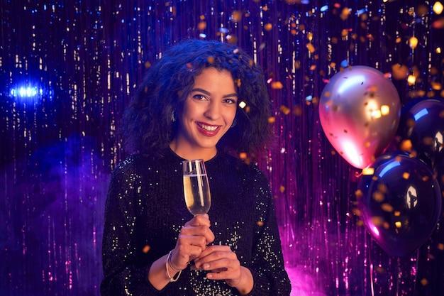 Portret van mooie gemengde ras vrouw met champagne glas en glimlachend in de camera terwijl u geniet van feest in nachtclub, kopieer ruimte Premium Foto
