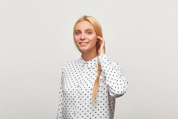 Portret van mooie ijverige blonde vrouw met blauwe ogen, staande in een halve draai corrigeert haar vlecht Gratis Foto