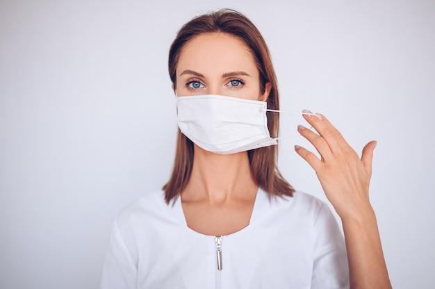 Portret van mooie jonge arts die beschermend masker draagt Premium Foto