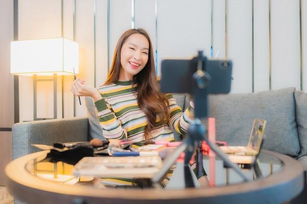 Portret van mooie jonge aziatische vrouw beoordelingen en maakt gebruik van cosmetica op de bank Gratis Foto