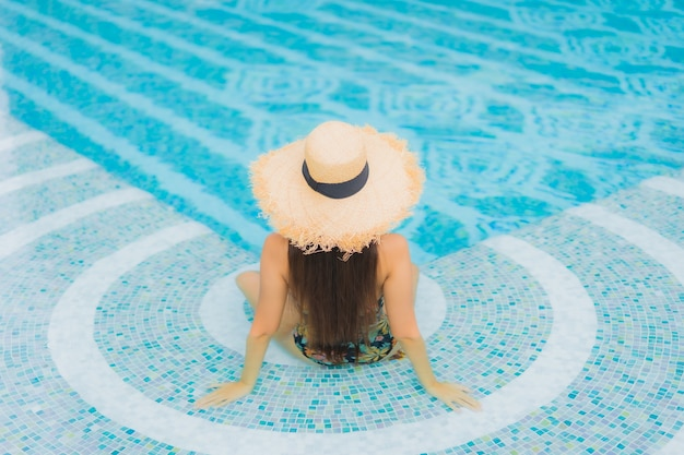 Portret van mooie jonge aziatische vrouw ontspant op het zwembad in hotelresort Gratis Foto