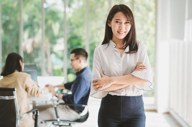 Portret van mooie jonge aziatische zakenvrouw staande armen gekruist met collega op achtergrond in de vergaderzaal in kantoor Premium Foto
