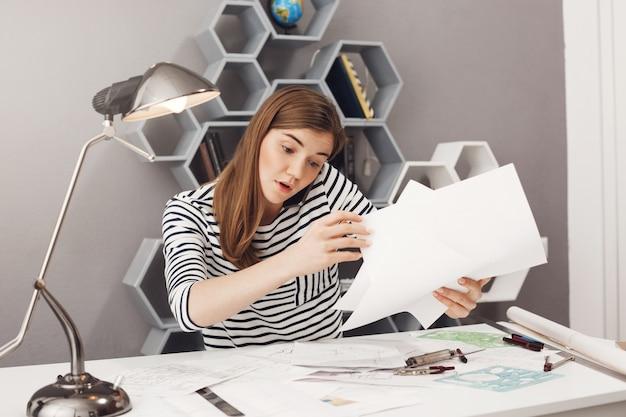 Portret van mooie jonge donkerharige geconcentreerde europese vrouwelijke freelance ontwerper praten aan de telefoon met teamleider, proberen om papieren te organiseren voor de vergadering van morgen. Gratis Foto