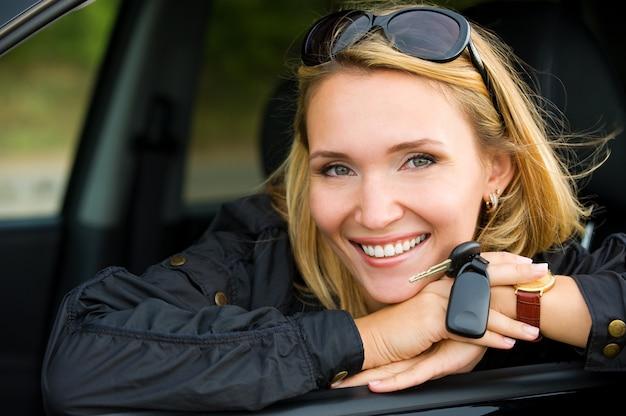 Portret van mooie jonge lachende vrouw in de nieuwe auto met sleutels - buitenshuis Gratis Foto