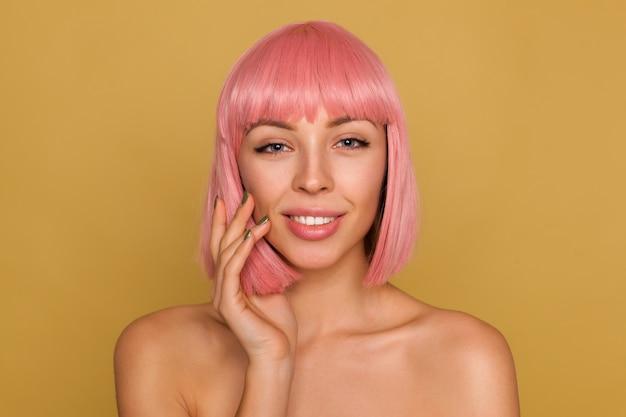 Portret van mooie jonge positieve vrouw met roze bob kapsel kijken met kalm gezicht en hand opheffen naar haar wang, poseren over mosterdmuur Gratis Foto