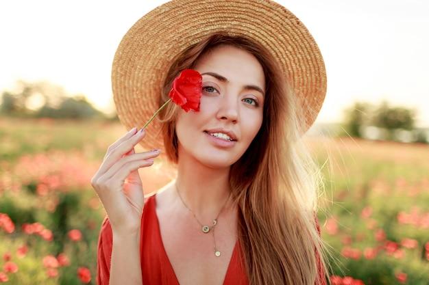 Portret van mooie jonge romantische vrouw close-up met papaver bloem in hand poseren op de achtergrond van een veld. het dragen van een strooien hoed. zachte kleuren. Gratis Foto