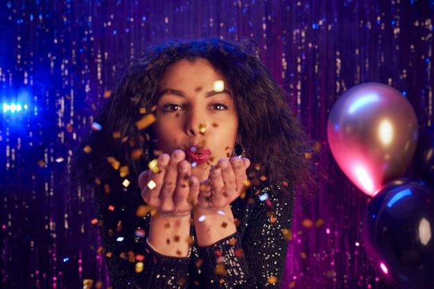 Portret van mooie jonge vrouw blazen glitter op camera close-up terwijl u geniet van feest in nachtclub, kopieer ruimte Premium Foto