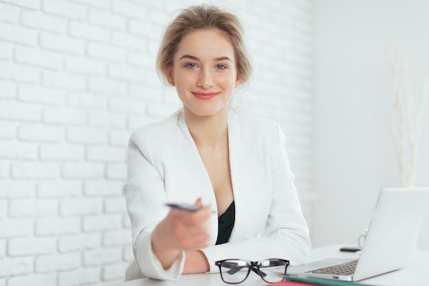 Portret van mooie jonge vrouw die in het bureau werkt. Premium Foto