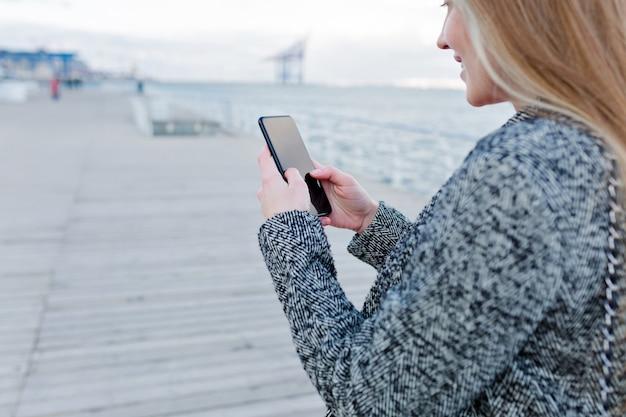 Portret van mooie jonge vrouw met een gelukkige glimlach in grijze vacht scrollen smartphone in de buurt van de zee Gratis Foto