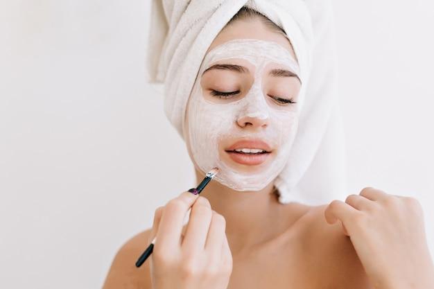 Portret van mooie jonge vrouw met handdoeken na bad nemen cosmetisch masker op haar gezicht. Gratis Foto