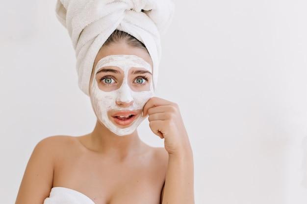 Portret van mooie jonge vrouw met handdoeken na bad nemen cosmetische masker en zorgen over haar huid. Gratis Foto