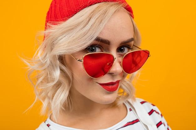 Portret van mooie jonge vrouw met kort blond krullend haar en lichte make-up in witte overall. rode zonnebril en rode hoed glimlacht geïsoleerd op oranje Premium Foto