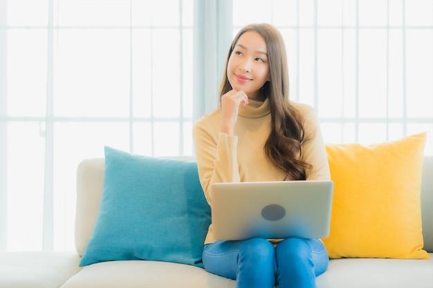 Portret van mooie jonge vrouw met laptop op de bank in de woonkamer Gratis Foto