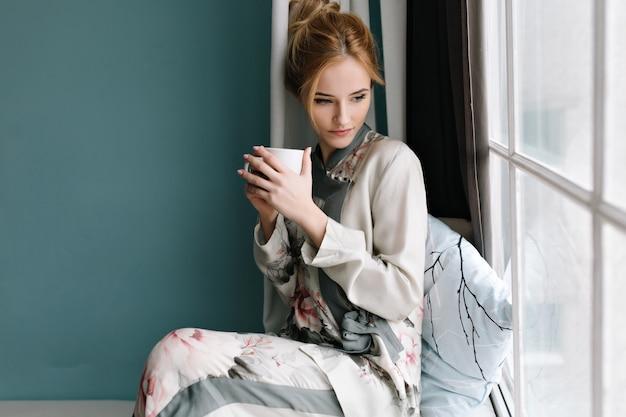 Portret van mooie jonge vrouw met sensuele blik door raam, zittend op de vensterbank met mok koffie in haar handen. turquoise muur. gekleed in een zijden pyjama met bloemen. Gratis Foto