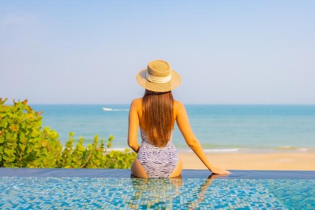 Portret van mooie jonge vrouw ontspannen op het zwembad Gratis Foto