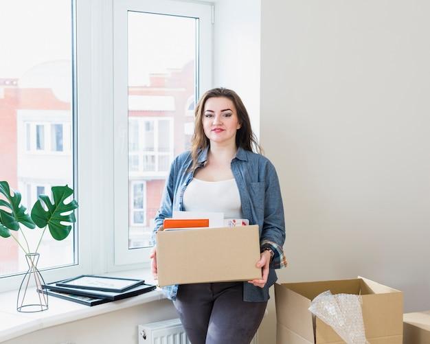 Portret van mooie jonge vrouw uitpakkende kartonnen dozen bij haar nieuwe huis Gratis Foto