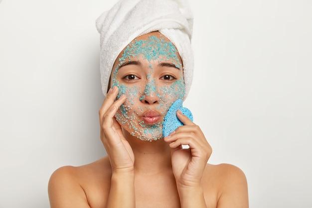 Portret van mooie jonge vrouwelijke looks met gevouwen lippen close-up, maakt zuiverheid peeling procedure, heeft een handdoek op haar hoofd, past zeezoutkorrels op het gezicht toe, houdt een spons vast voor het afvegen van de huid Gratis Foto