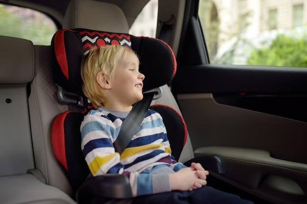Portret van mooie kleine jongenszitting in autostoel. veiligheid van kinderen Premium Foto