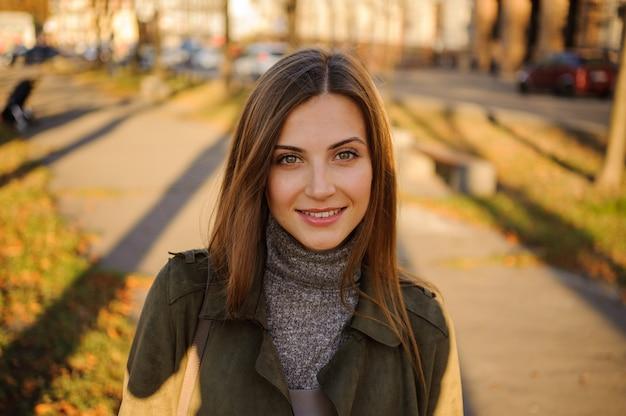 Portret van mooie lachende jonge vrouw in park. Premium Foto