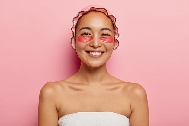 Portret van mooie lachende vrouw heeft cosmetische behandelingen close-up, draagt roze douchemuts, gewikkeld in een handdoek, heeft collageen pads onder de ogen om rimpels te verminderen, staat binnen. schoonheid concept. Gratis Foto