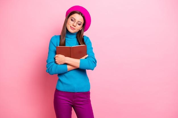 Portret van mooie meisjesachtige meisje verslaafde nerd geek knuffel haar favoriete boek geniet van herfst vrije tijd dichte ogen dragen blauwe paarse outfit. Premium Foto
