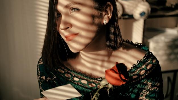 Portret van mooie meisjeszitting door venster bij zonsondergang en dromerig kijkend uit venster Premium Foto