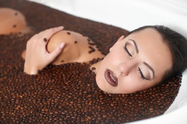 Portret van mooie mode vrouw in jacuzzi met koffie. lichaamsverzorging. lichte make-up Gratis Foto