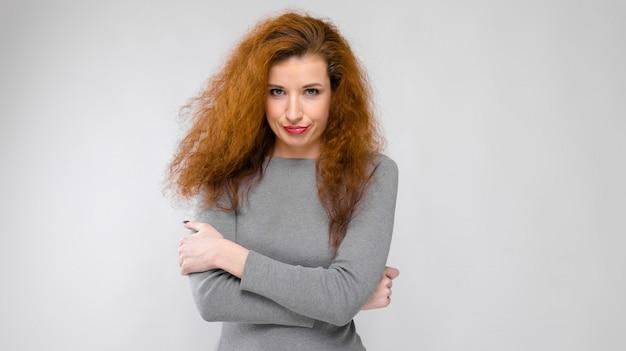 Portret van mooie roodharige ongelukkige jonge vrouw in grijze kleren op grijze achtergrond Premium Foto