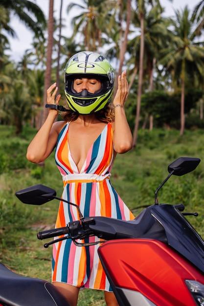 Portret van mooie ruiter vrouw in geelgroene motorhelm en kleurrijke lichte zomerjurk in de jungle op tropisch veld onder palmbomen. Gratis Foto