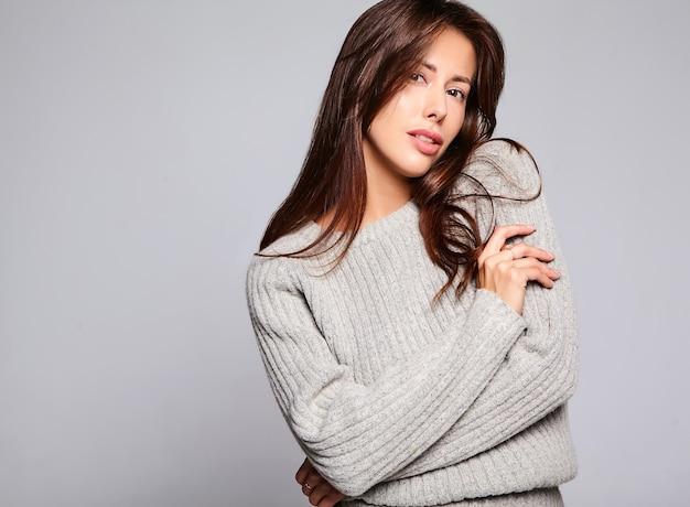 Portret van mooie schattige brunette vrouw model in casual herfst grijze trui kleding zonder make-up geïsoleerd op grijs Gratis Foto