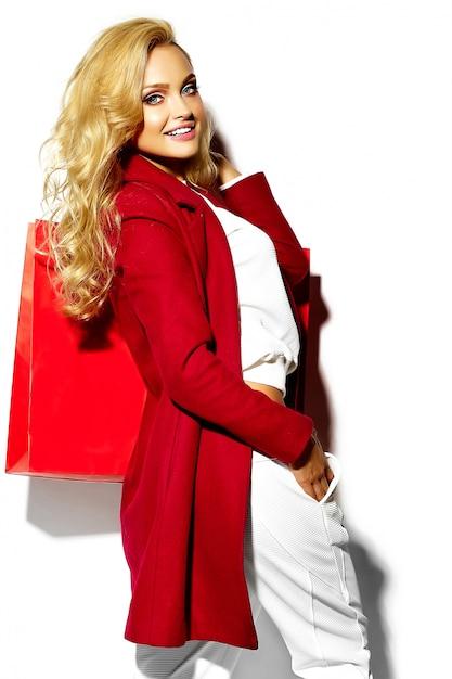 Portret van mooie schattige gelukkig lieve lachende blonde vrouw meisje bedrijf in haar handen grote boodschappentas in hipster rode kleding op wit wordt geïsoleerd Gratis Foto