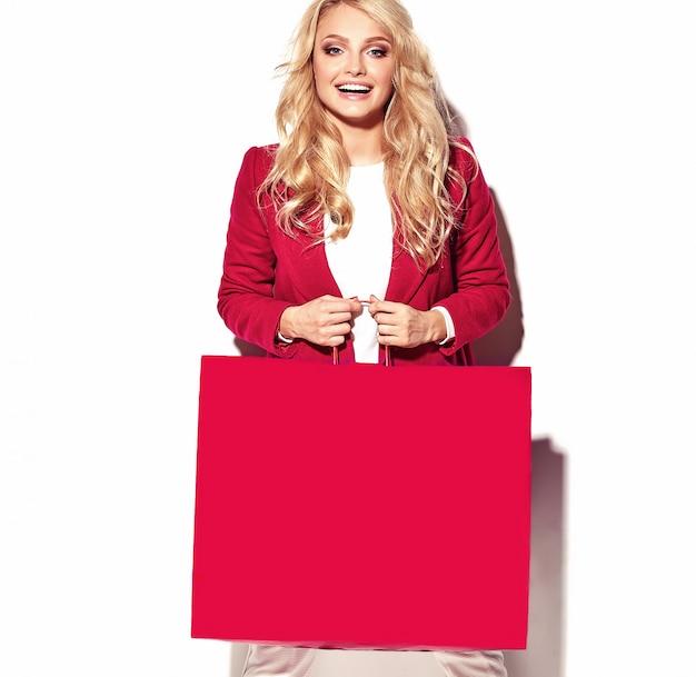 Portret van mooie schattige gelukkig zoete verrast blonde vrouw meisje bedrijf in haar handen grote boodschappentas in hipster rode kleding op wit wordt geïsoleerd Gratis Foto